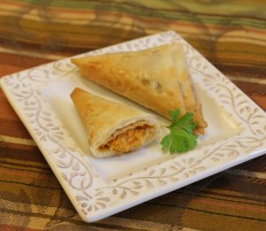 two sweet potato phyllo triangles on plate
